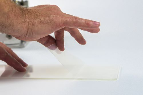 2: Fold back a few centimetres of the adhesive cover on an Acrylic Face.