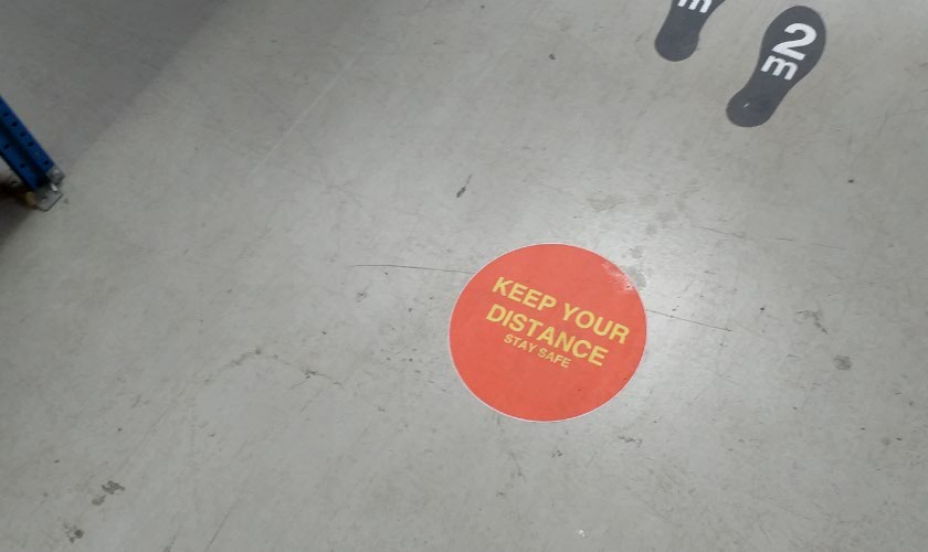 Red Keep Your Distance Floor Sticker in use